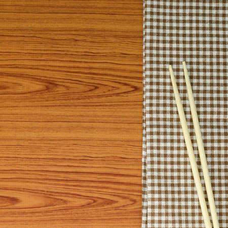 chopsticks with kitchen towel on wood background photo