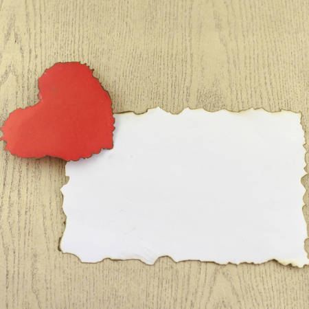 heart and white paper on wood background photo