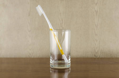 toothbrush in glass on wood