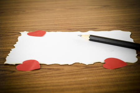 white paper with pencil and red heart on wooden background concept for valentine day photo