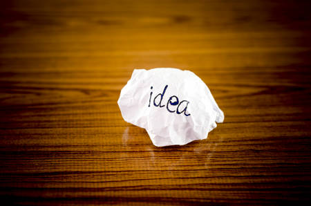 writing idea word on crumpled on wood background photo
