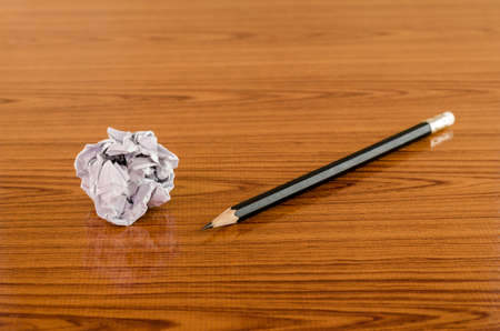 crumpled paper and pencil on wood background photo