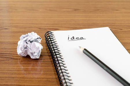 crumpled paper and pencil with notebook write idea word on wood background photo
