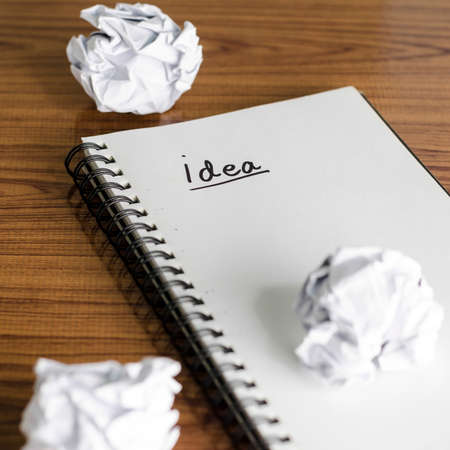 notebook write idea word with crumpled on wooden background photo