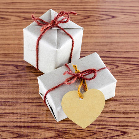 brown gift box with heart tag card on wood background photo