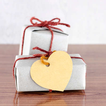 brown gift box with heart tag card on wood background