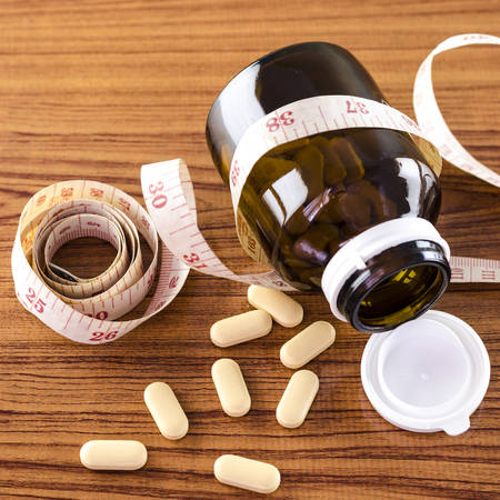 pills and measuring tape concept diet with drug Stock Photo