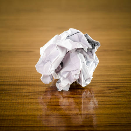 wastrel: crumpled paper on wood background Stock Photo