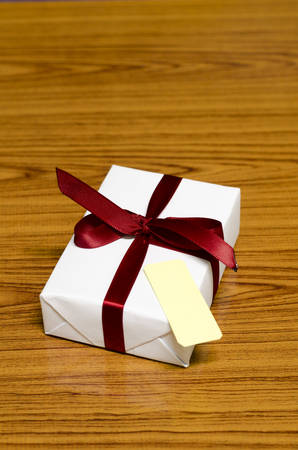 ribbin: white gift box and red ribbin with tag on wood background Stock Photo