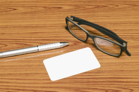 business card and pen with glasses on wood background photo