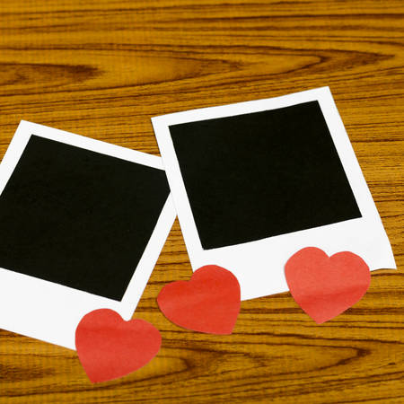 photo frame with heart on wood background photo