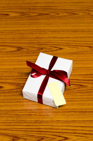 white gift box and red ribbin with tag on wood background photo