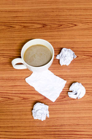 coffe cup and crumpled for idea on wood background photo