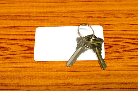 business card and keys on wood background photo