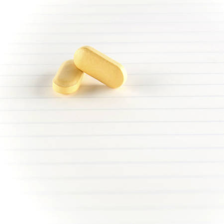 seriousness: two pills on notebook concept seriousness Stock Photo