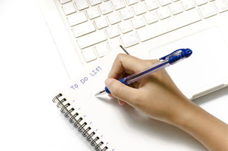 woman hand writing with pen on notebook write to do word and laptop over white background photo