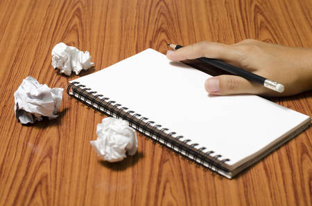 hand writing on notebook with crumpled paper on wood table background Imagens