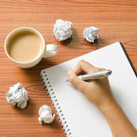 woman hand writing with pen on notebook.there are crumpled paper and coffee cup on wood table background