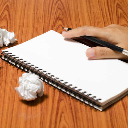 hand writing on notebook with crumpled paper on wood table background photo