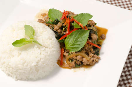 Thai main food Rice topped with stir-fried pork and basil photo