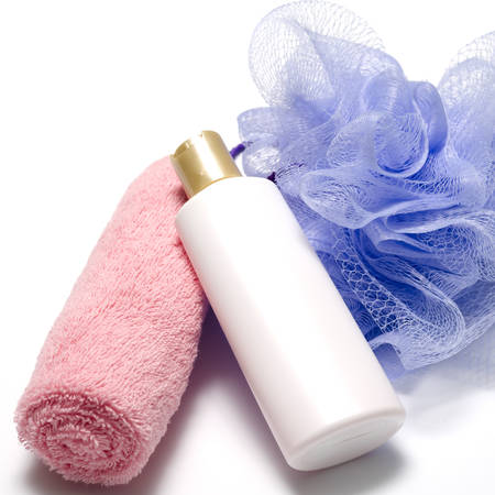 purple bath puff liquid soap and pink towel on a white background