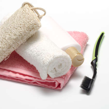 bedlinen: towel loofah liquid soap and toothbrush on a white background