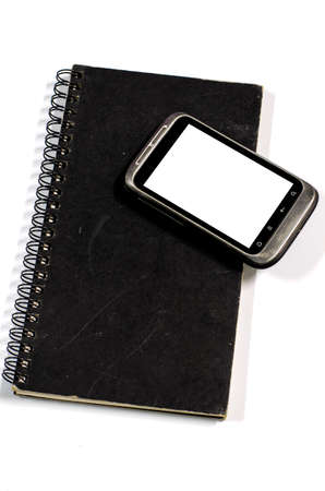 smartphone on note book on a white background Stock Photo