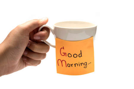 hand holding coffee cup with sticky note write Good morning isolated on white background Stock Photo