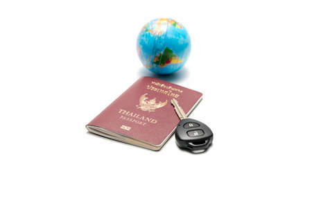 passport car key and earth ball isolated on white background concept drive around the world Stock Photo