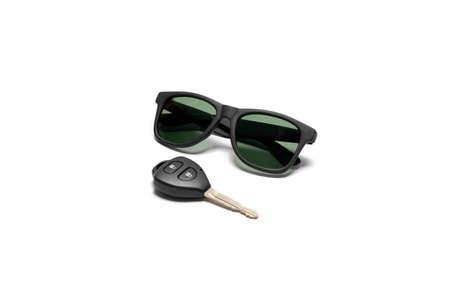 llave de sol: gafas de sol y la llave del coche aislado en el fondo blanco