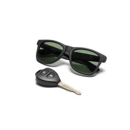 clave sol: gafas de sol y la llave del coche aislado en el fondo blanco