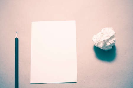 writer's block: Pencil on clear white paper with crumble paper balls on brown color background vintage style