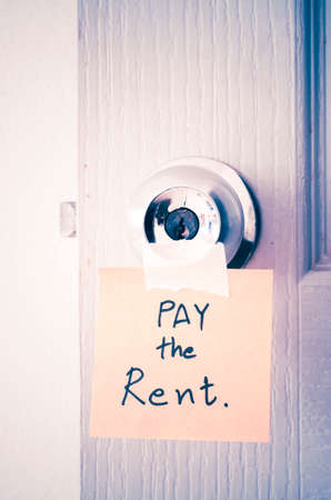 latch: sticky note write a message pay the rent on the latch door vintage style