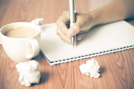 write a letter: woman hand writing with pen on notebook.there are crumpled paper and coffee cup on wood table background vintage style