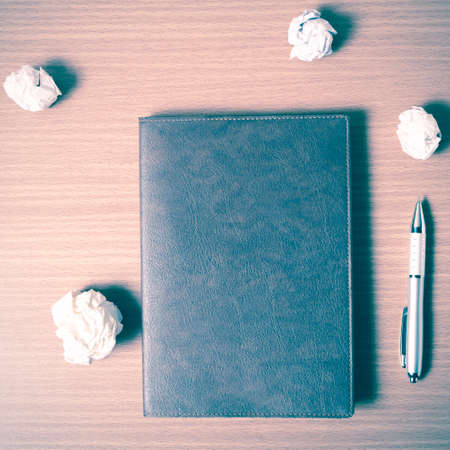 writer's block: brown notebook and crumpled paper on wood background vintage style