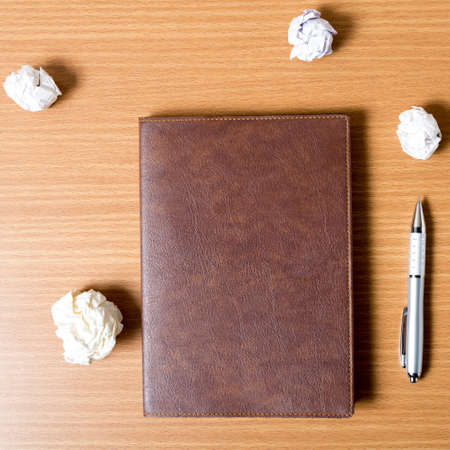 writer's block: brown notebook and crumpled paper on wood background