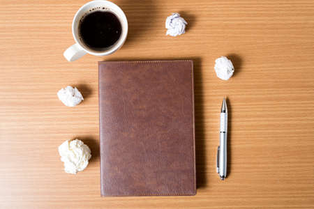 writer's block: brown notebook and crumpled paper with coffee cup on wood background