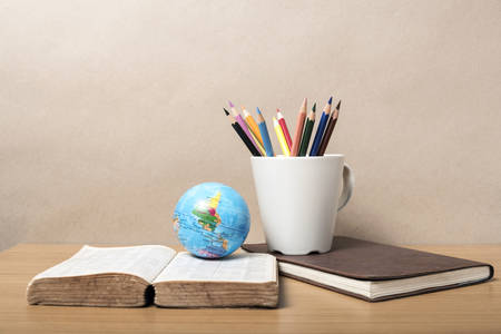 book and earth ball with color pencil on wood background