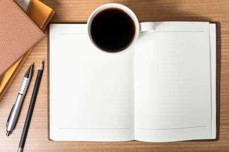 open notebook with book and coffee cup on wood background