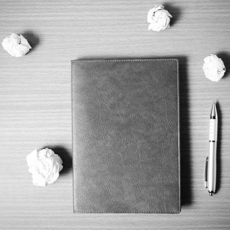 writer's block: notebook and crumpled paper on wood background black and white color tone style