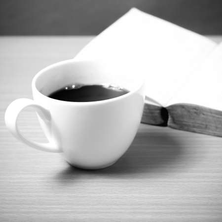 old desk: open book with coffee on wood background black and white color tone style Stock Photo