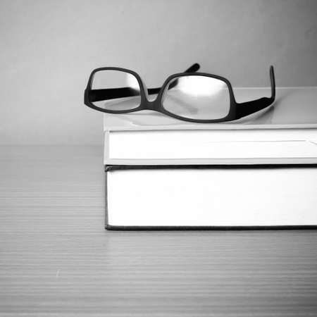 Study Desk: book and eyeglasses on wood background black and white color tone style