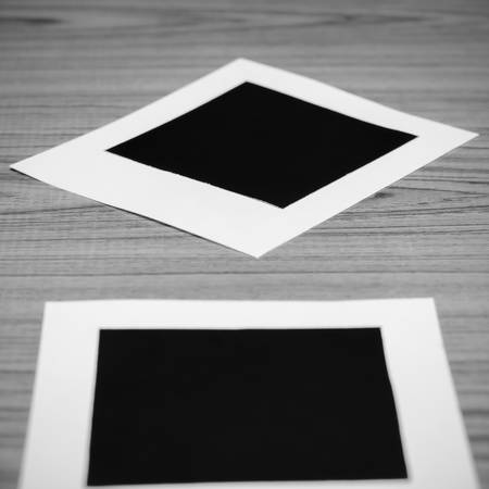 white polaroids: photo frame on wood background black and white color tone style
