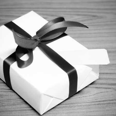 ribbin: gift box and ribbin with tag on wood black and white color tone style