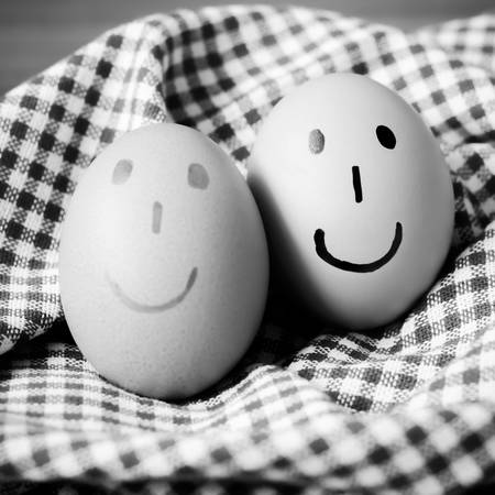 brown egg: smile love egg couple in brown kitchen towel on wood table black and white color tone style Stock Photo