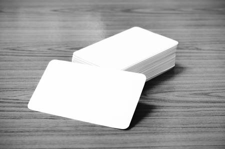 stack of business card on wood background black and white color tone style