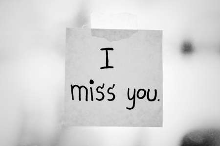 letter memo: I miss you word sticky note on window mirror black and white color tone style