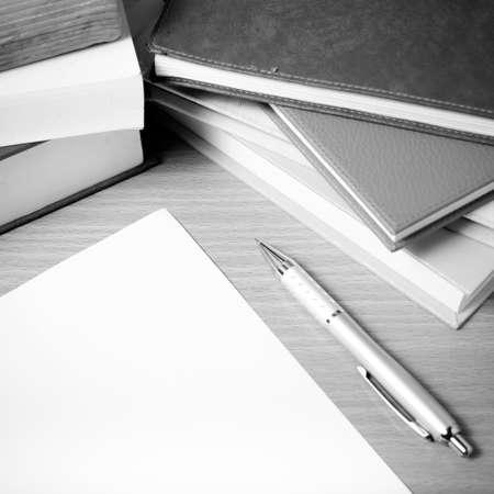 pluma de escribir antigua: empty paper and pen with book on wood background black and white tone style Foto de archivo
