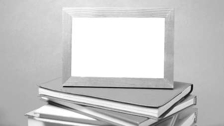 antique frames: stack of book and photo frame on wood background black and white tone style Stock Photo