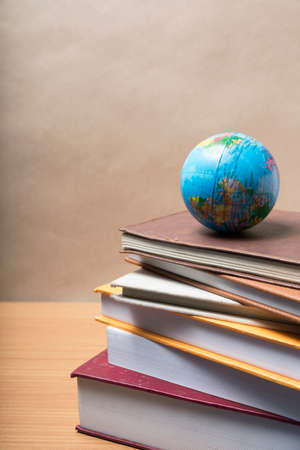 stack of book and earth ball on wood background